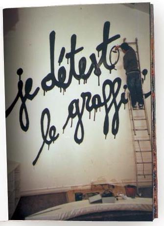 Chico subido a una escalera pintando un graffitti en una pared con el texto Je d'etesto le graffitti